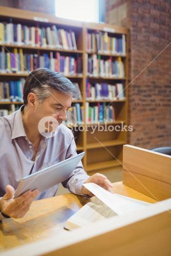 Professor holding digital tablet and reading book