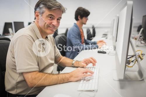 Portrait of happy professor working on computer