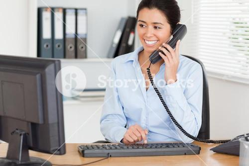 Attractive woman on the phone while typing on a keyboard
