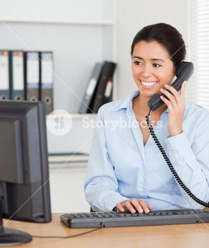 Beautiful woman on the phone while typing on a keyboard