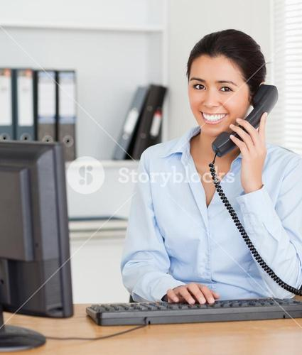 Good looking woman on the phone while typing on a keyboard