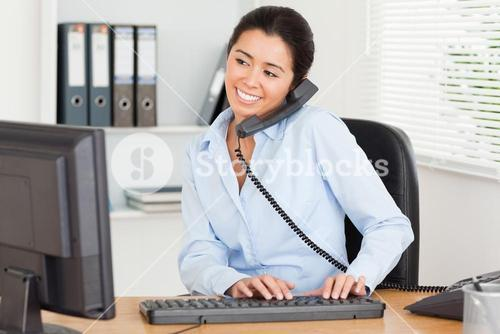 Cute woman on the phone while typing on a keyboard
