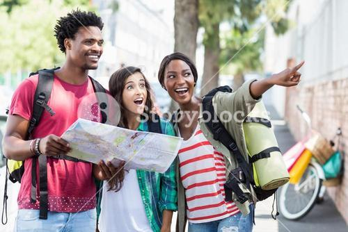 Friends holding map and pointing
