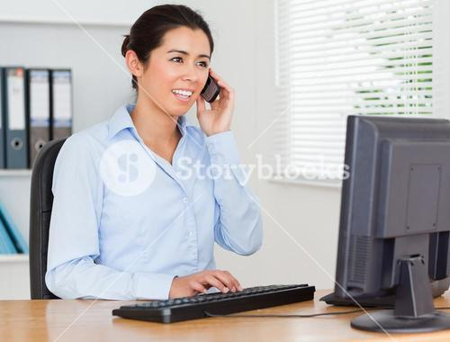 Pretty woman using her mobile phone while typing on a keyboard