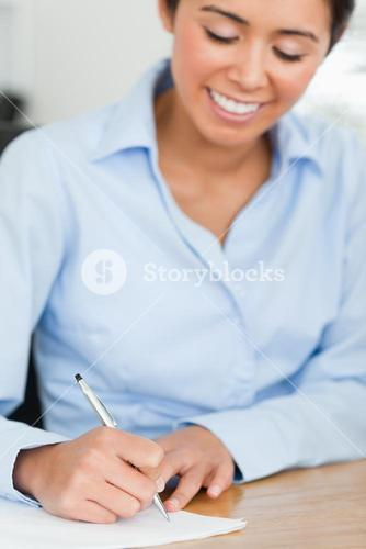 Frontal view of an attractive woman writing on a sheet of paper while sitting
