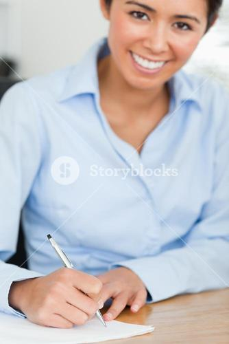 Frontal view of a charming woman writing on a sheet of paper while sitting