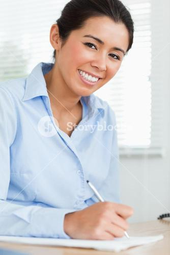 Good looking woman writing on a sheet of paper while sitting