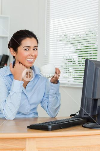 Beautiful woman enjoying a cup of coffee while looking at a computer screen