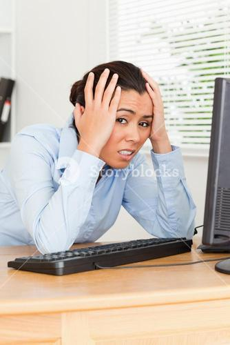 Pretty upset woman looking at a computer screen while sitting