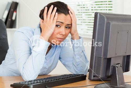 Lovely upset woman looking at a computer screen while sitting