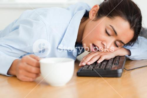 Pretty woman sleeping on a keyboard while holding a cup of coffee