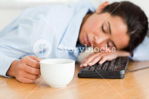Beautiful woman sleeping on a keyboard while holding a cup of coffee