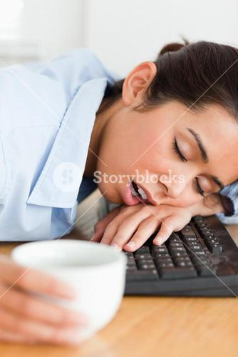 Good looking woman sleeping on a keyboard while holding a cup of coffee