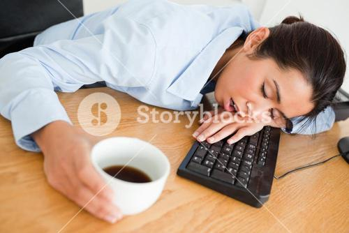 Attractive woman sleeping on a keyboard while holding a cup of coffee
