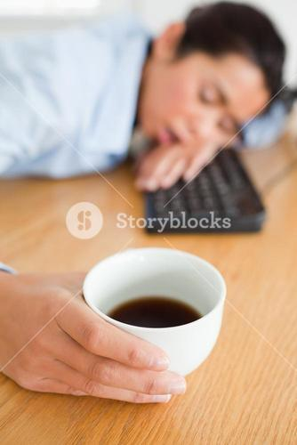 Cute woman sleeping on a keyboard while holding a cup of coffee