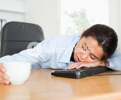 Frontal view of a beautiful woman sleeping on a keyboard while holding a cup of coffee