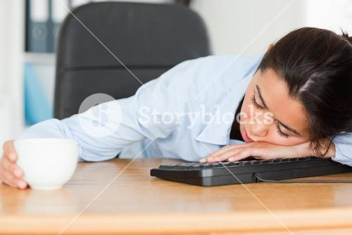 Frontal view of a good looking woman sleeping on a keyboard while holding a cup of coffee