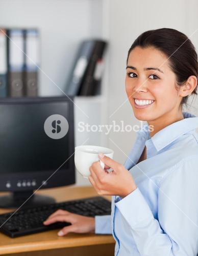 Pretty woman holding a cup of coffee while sitting