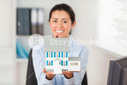 Lovely woman holding a miniature house while looking at the camera