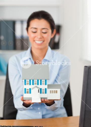 Pretty woman holding a miniature house while looking at the camera