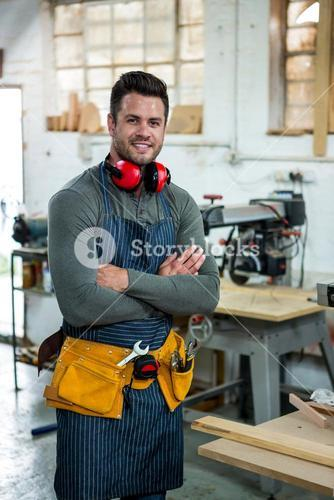 Carpenter smiling and crossing arms