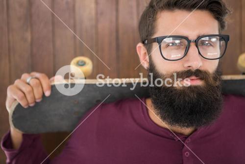 Hipster posing with his skateboard