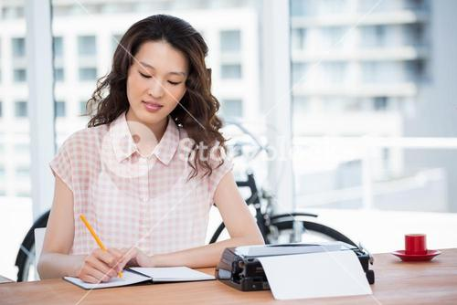Hipster woman writing on her notebook