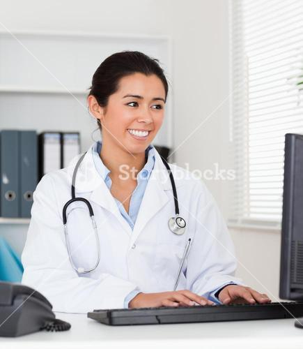 Beautiful woman doctor typing on a keyboard