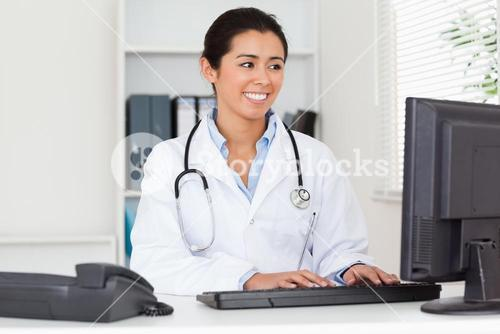 Attractive woman doctor typing on a keyboard