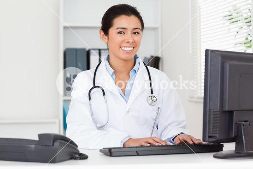 Good looking woman doctor typing on a keyboard