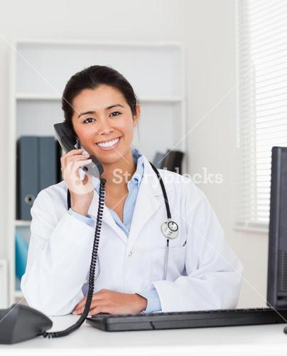 Good looking woman doctor on the phone while sitting