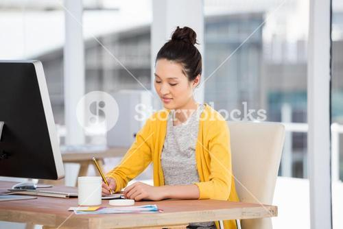 A working girl is writing at her desk