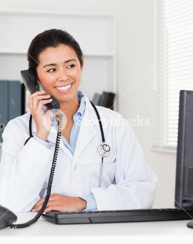 Beautiful woman doctor on the phone while sitting
