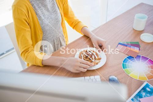 Woman eating breakfast at work