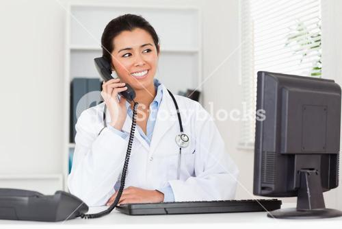Attractive woman doctor on the phone while sitting