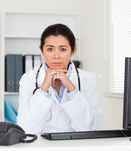Beautiful worried woman doctor looking at the camera while sitting