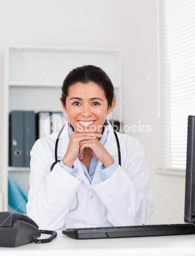 Beautiful woman doctor posing while sitting