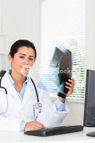Good looking female doctor looking at a xray
