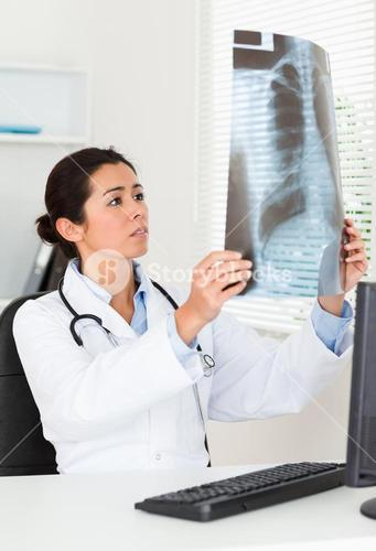 Pretty female doctor looking at a xray