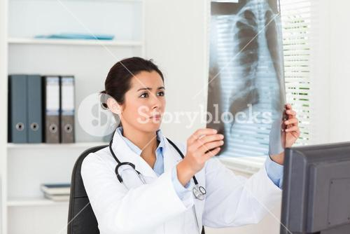 Gorgeous female doctor looking at a xray