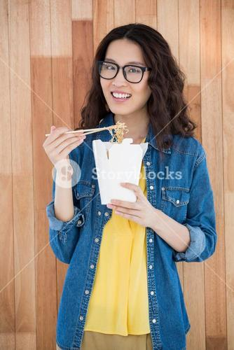 Hipster eating with chopsticks