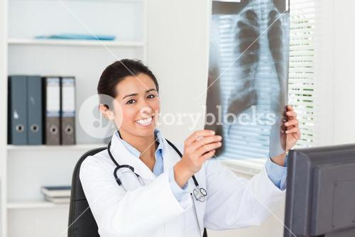 Lovely female doctor looking at a xray