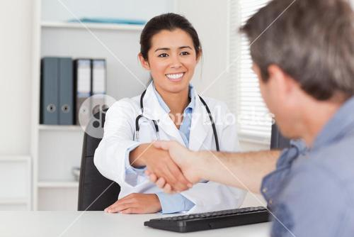 Pretty female doctor shaking a patients hands