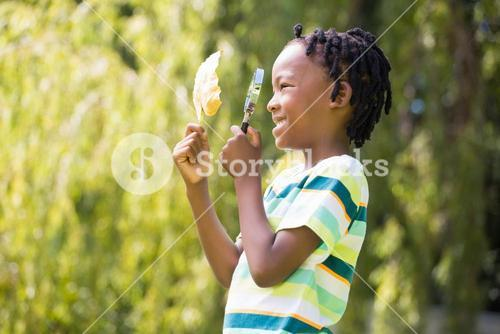 Profile view of boy looking at leaf through magnifying glass