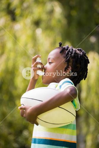 Profile view of a kid using an asthma inhaler