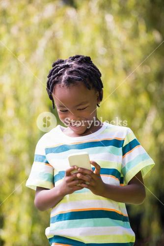 A kid playing with a mobile phone