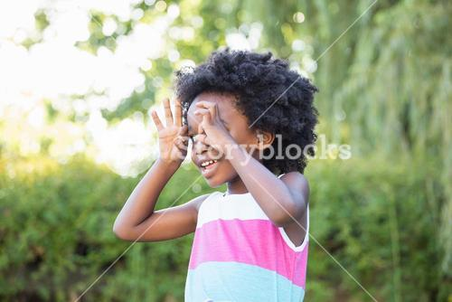 A kid putting her hands like glasses