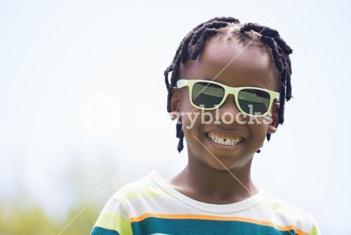 A kid with sunglasses smiling
