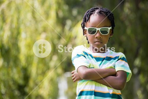 A kid with sunglasses crossing his arms