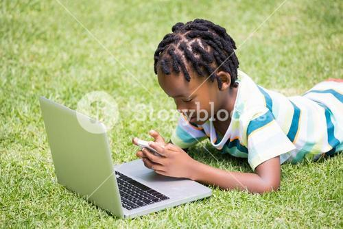 A kid looking his mobile phone and laptop